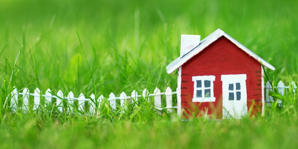 miniature red house and white fence on grass