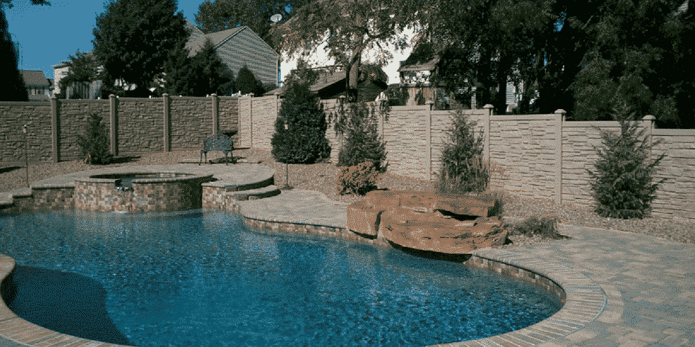 Backyard simulated stone fence surrounding a pool for privacy