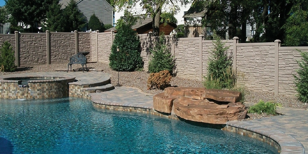 Faux stone fences surrounding a backyard pool