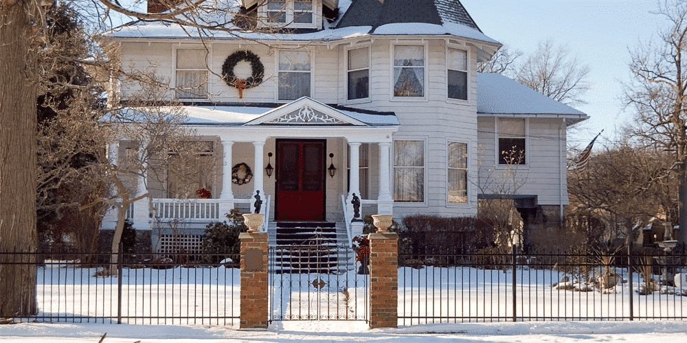 snowy setting with a house with a winter fence installed