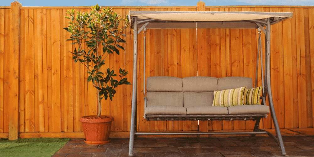 swing chair and a plant in front of a brown fence that can be provided by a St. Louis Fence Company